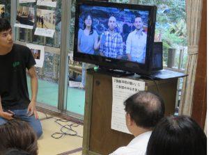 ウィーンからのビデオメッセージを見る京都のシンポジウム参加者たち。左端が阿比留高広君