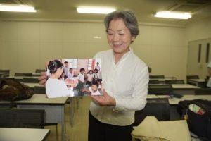 フランシスコさん撮影の子供の写真を手に笑顔の被爆者・花垣ルミさん(フランシスコさん写す)