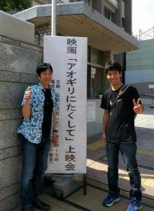 正門の告知看板の前で(左から、音楽監督・伊藤茂利さん、サポーター・阿比留高広さん)