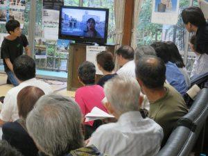 ウィーンからのビデオメッセージに見入るシンポジウム参加者たち。